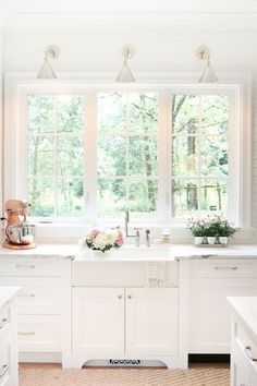 Triple window, farmhouse sink, sconces. Nice light and bright cabinet and countertop colors.