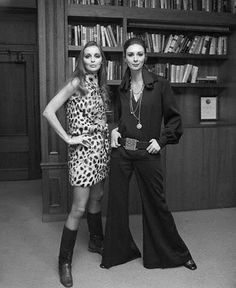 Fashion model Wilhelmina, whose face graced the covers of over 300 magazines before retiring, models a pair of black flared pants and shirt with top model Samantha Jones, wearing a leopard skin dress, 1969.