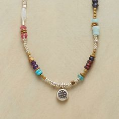 """More The Merrier Necklace Item No. 64024 $128.00 A handmade gemstone beaded necklace that brings together a lovely array of lusters and hues.  Numerous gems of coral, carnelian, turquoise, iolite, garnet, apatite, amethyst, mystic pink quartz, moonstone, labradorite, citrine, purple jade and amazonite appear in segments of this handmade gemstone beaded necklace, or alone amid a mix of metals. Brass and sterling silver beads, sunburst charm, lobster clasp. 17"""" to 18-1/2""""L."""