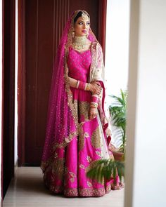 Fuschia pink bridal lehenga matched up with gold aad necklace. Gold Lehenga, Bridal Lehenga Choli, Party Sarees, Trendy Sarees, Lehenga Choli Online, Latest Designer Sarees, Pink Gowns, Lehenga Collection, Bridal Outfits
