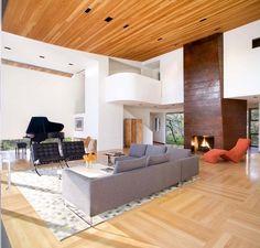 fauteuils design en cuir noir, canapé en tissu gris et cheminé acier corten