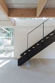 Black steel staircase with slender handrail and wooden treads. Project North Vancouver House …