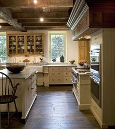 interior design Beautiful wood molding and beams in this traditional kitchen. Glass upper cabinets, marble countertop, hardwood floor, ... Love the look!