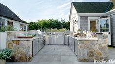 """The U-shaped layout of this Nantucket kitchen is zoned from hot to cold, moving from the K900 Hybrid Fire Grill on the left to a pair of 32,000-BTU cooktops, the Outdoor Artisan pizza oven, a sink, two 24-inch refrigerator drawers, a beverage cooler, and a 15-inch ice maker. """"Usually an outdoor kitchen is more of an adjunct, but this is complete,"""" designer Kris Horiuchi says. """"The client wanted the whole shebang - grill, cooktops, refrigerator, sink, pizza oven.""""   - HouseBeautiful.com Modular Outdoor Kitchens, Rustic Outdoor Kitchens, Simple Outdoor Kitchen, Outdoor Kitchen Bars, Outdoor Kitchen Cabinets, Outdoor Dining, Outdoor Kitchen Design, Outdoor Decor, Family Kitchen"""