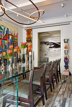 In the dining room a Niamh Barry chandelier hangs above a glass-and-chrome table from DDC NYC. Two Charlie Roberts wood sculptures flank the room's entrance.