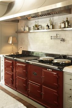 """The flamboyant double Aga capped by the dramatic """"awning"""" style range hood. All of the oils, salts, etc on the shelf were purchased specifically for this photo shoot - """"prop"""" shopping is one of my most favorite """"styling"""" activities."""