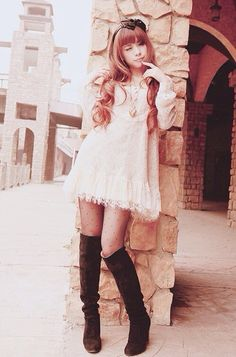 A very cute white layered lace dress with knee high black tights.