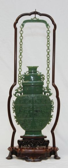 "Chinese Archaic Jade Hanging Covered Urn.- A large Chinese hanging urn having a very finely carved and textured high relief archaic design to body. Relief carved chih lung dragon and phoenix arms with rings. Includes tiered wooden stand and fitted presentation box. Urn measures approx.12 1/2"" height x 7 3/8"" width (31.7cm x 7.3cm). Overall height with chain and hanging apparatus 21"" height (53.3cm)."
