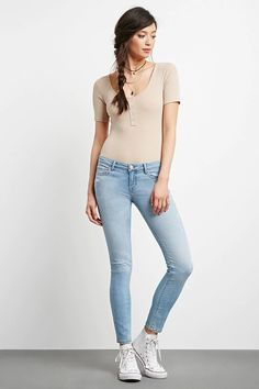 A pair of low-rise skinny jeans with distressed detailing throughout, a zip fly, and a five-pocket construction. #thelatest