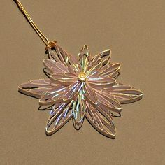 Make this folded paper flower pendant (or snowflake ornament, depending on the season!)