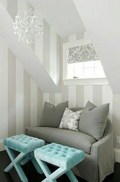 canapé gris intérieur moderne, lustre baroque de couleur blanc, mur aux rayures blanc gris