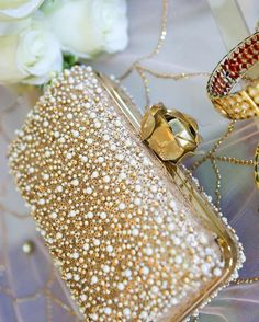 This Gold Moti clutch by @ClutchdBags with an array of pearls and beads set against the background of gold sequins and a gold rose lock adds an extra bling to a bridal look.  Photo Courtesy- @ShreyaSenPhotography (Mumbai)
