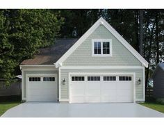 White carriage house style garage doors on a detached garage door. Can be constructed in wood or low-maintenance insulated steel. www.clopay.com