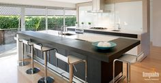The striking island unit enables practical seating and the lower bench top . Kitchen Island Bench, Kitchen Carts, Contemporary Kitchen Island, Kitchen Benchtops, Building A New Home, Open Plan Kitchen, Kitchen Ideas, Kitchen Styling, Bathroom Renovations