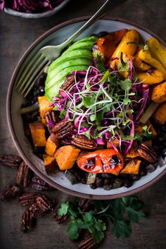 Vegan Mexican-style, Oaxacan Bowl with roasted chipotle sweet potatoes and sweet peppers over a bed of warm seasoned black beans. Topped with a crunchy cabbage slaw, avocado and toasted Chipotle Maple Pecans.   www.feastingathome.com