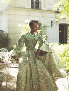 "Fresh Feeling - Dior designer Raf Simons describes Lupita as ""radiant . . . she seems to take such pleasure in playing with fashion."" Here she reflects the leaves in the garden of Hôtel Particulier Montmartre. Dior Haute Couture silk-faille coat and Dior Fine Jewelry bracelet."