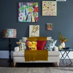 The jewel bright cushions and artwork add a real sense of vibrancy to this rich grey space