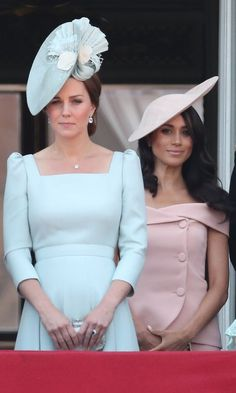 (L-R) Catherine, Duchess of Cambridge looking seriously chic in a powder blue Alexander McQueen custom dress with her statement fascinator by milliner, Juliette Botterill, while Meghan, Duchess of Sussex stunned in a pretty pink off-the-shoulder Carolina Herrera dress and a matching hat by Philip Treacy, as they watch the flypast on the balcony of Buckingham Palace during Trooping The Color 2018 in London, England.