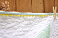 Scalloped edge on binding using yellow ric rac.  Sew your ric rac around the very edge of the quilt before sewing your binding on.  Then sew your binding right on top of it. Finish binding as usual.