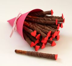 Chocolate dipped pretzel sticks with candy hearts on top.