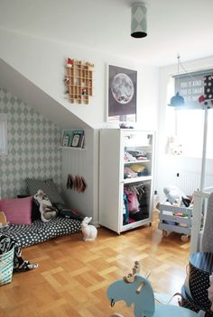 Kidsroom with Scandinavian details. Ferm Living harlequin wallpaper in dusty green on wall and light fixture. Polka dot bedding. Mr. Moon print, designed by Martin Krusche and silkscreen printed by hand.