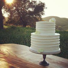 Simple two-tier while wedding cake by Enjoy Cupcakes of Los Olivos, California; photo by groom Jose Villa