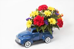 Teleflora's Ford Pickup Bouquet A ceramic model of the 1948 Ford pickup truck holds an all around mounded arrangement of carnations, spray roses, daisy poms and purple statice. x Item# 1106 Little Blue Trucks, Spray Roses, Carnations, Pickup Trucks, F1, Fathers Day, Flower Arrangements, Daisy, Bouquet