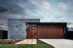 Horizontal slabs of bluestone and vertical hardwood slats on the exterior of the house. Tagged: Exterior, Wood Siding Material, Flat RoofLine, House, and Stone Siding Material. Photo 1 of 13 in A Striking Courtyard Awaits Behind These Bluestone Walls