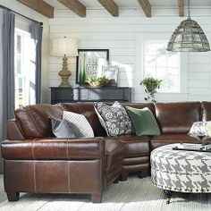 Leather Sectional and colors/patterns of the room keep the space light and airy.