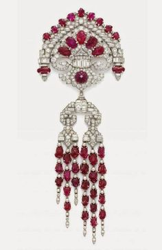 An art deco carved ruby, diamond, and platinum brooch, by Lacloche Frères, Paris, circa 1930's.