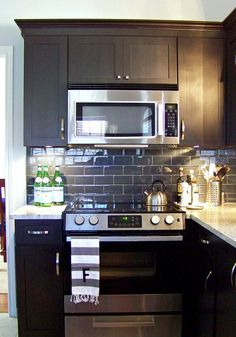 Black cabinets, granite countertops and a pretty subway tile backsplash.