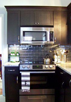 Black cabinets, granite countertops and a pretty subway tile backsplash.