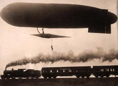 Zeppelin  with man dangling from a rope flies over German train 1925