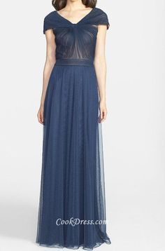 Navy blue long tulle bridesmaid dress has sheer tulle covering nude stretch satin, giving shrug with volume pleats and cap sleeves, long tulle skirt flows with ruched band, v back below zipper closure.