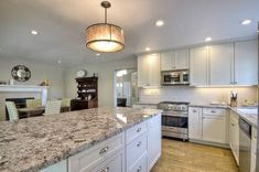 Beautiful Granite Countertops on top of White Cabinets and Basketweave Backsplash