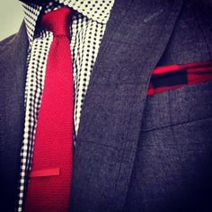 In the example to the left I'm wearing a beautiful charcoal grey shadow plaid suit from Indochino.com. The pattern is subtle and subdued. I chose to accent it by wearing black and white tightly checked gingham shirt (also from Indochino). The gingham pattern is echoed in the red cotton pocket square, and, in turn, the red silk knit tie pairs to the pocket square nicely. The pièce de résistance, however, if you ask me, is the small 1.5 inch matte red anodized aluminum tie bar. It's almost…