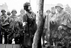 Men of the Wermacht view the hanged corpse of a young girl. Probably a Russian resistance member (though she conspicuously wears a red cross band on her right arm), she likely was tortured and raped before her death.  Of the soldiers in the picture, only the one nearest the camera is unsmiling, and his face betrays only indifference for his victim. Some of these men probably had daughters the same age as the girl they hanged. Still, they smile.