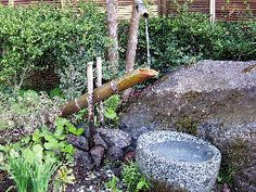 A shishiodoshi is garden device, made of bamboo and wood, designed to scare away birds. As the bamboo tube fills with water, it clacks against a stone, empties, then fills with water again.