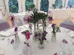 Shades of purple and crimson seasonal flowers in an array of jars for your guest tables