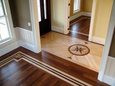 """Beautiful craftsmanship in this wood inlaid floor pattern.  The lighter trim gives the room dimension and the adjacent hallway with the lighter wood with a """"nautical"""" inlaid pattern is a nice break between the two dark floors. 