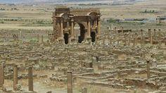 Terletak di lereng Aures Massif, sekitar 35 km sebelah timur dari kota Batna, di yang saat ini adalah wilayah Aljazair. Dibangun hampir 2.000 tahun yang lalu, oleh Kaisar Romawi Trajan, Grid plan merupakan sistem pola jalan bersudut siku atau grid, pada kota kuno romawi dengan di mana bagian-bagian kotanya dibagi sedemikian rupa menjadi blok-blok empat persegi panjang dengan jalan-jalan yang paralel. Jalan-jalan di dalamnya dengan demikian menjadi tegak lurus satu sama lain.
