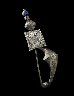 Silver Fibula with a Glass Bead Period: Fifth century BC Category: Etruscan Dimensions: 12.2 cm H Etruscan craftsmen were famous in antiquity for the complexity and sophistication of their metalwork. They were especially noted for their silver-working techniques.
