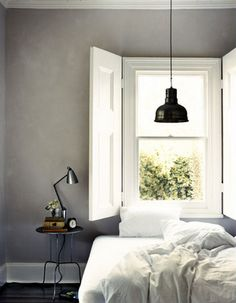 Grey and white bedroom with simple lamp and gorgeous sash windows with shutters. Love it.