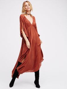 That Girl Maxi Dress | Easy and breezy semi-sheer crinkly maxi dress pieced with crochet trim throughout. Plunging V-neckline in front and low back with an adjustable tie at the back neck. Wide flutter sleeves with slit detailing. Asymmetrical hem with side vents.