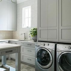 Gray Laundry Room Cabinets with Silver Front Load Washer and Dryer