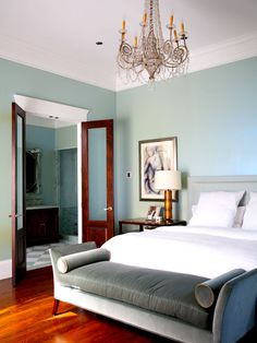 white moldings and bedding, dark wood floors and doors, gray-blue walls, light grey clean lined headboard, and plush velvet footer. bathroom has beautiful matching stain, tiles, and shower.