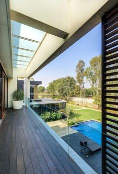 View of the poolscape and backyard from deroom balcony - Decoist Shop Front Design, House Design, New Delhi, Delhi India, Hanging Fireplace, Wood Interior Design, Exterior Design, House With Balcony, Residential Architecture