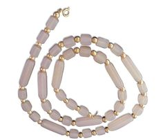 This feminine strand of beads is a great way to dress up a casual outfit. Comprised of beautiful pale, pink beads accentuated with gold spacers.