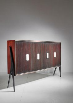 A large and elegant highboard, by Osvaldo Borsani, from the 1950s. It is made of mahogany with rare alabaster rounded grips. Other nice details are the polished maple on the inside, the dark finish on the outside and the golden inlay around the edges. A rare piece in absolute mint condition.