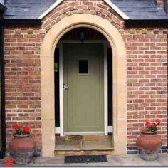 Sage green front door with red brick